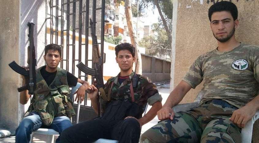 3 insurgés postés devant un immeuble contrôlé par l'ASL. Photo : Intégrales Productions.